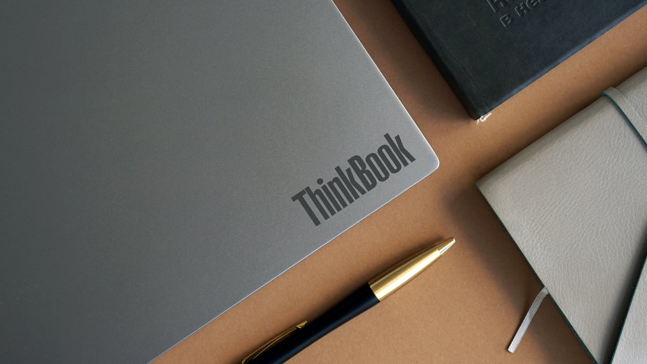 Thinkbook laptop with lid closed on desk with pen and day planner